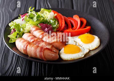 Petit-déjeuner anglais: Porcs dans des couvertures saucisses frites enrobé de bacon, oeufs, salade de légumes et sauce close-up sur une plaque sur une table horizontale. Banque D'Images