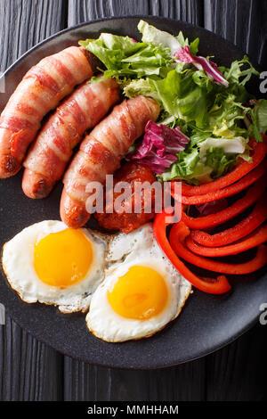 Saucisses frites enrobé de bacon, oeufs et salade fraîche gros plan sur une assiette. Haut Vertical Vue de dessus Banque D'Images