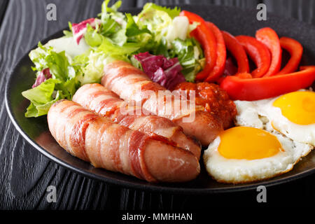 Les porcs en petit-déjeuner saucisses frites couvertures enrobé de bacon, d'œufs, de la sauce et salade fraîche gros plan sur une plaque horizontale. Banque D'Images