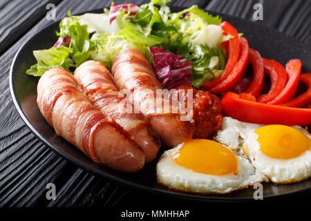 Repas complet: Porcs dans des couvertures saucisses frites enrobé de bacon, d'œufs, de la sauce et salade fraîche gros plan sur une plaque horizontale. Banque D'Images