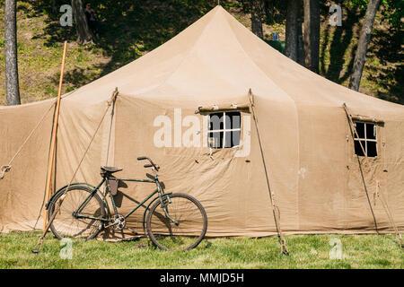 L'ancien Rareté Location stationné près de la grande toile de tente kaki militaire soviétique sur l'herbe verte dans la forêt de l'été ensoleillé.