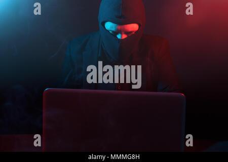 Pirate informatique en colère en fonction de vol de données de l'ordinateur portable allumé en rouge et bleu clair Banque D'Images