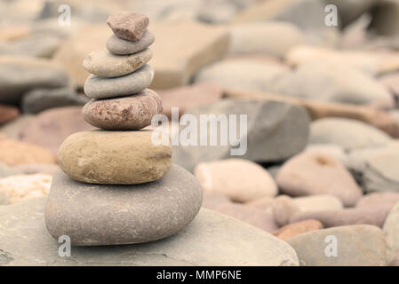 Tas de pierres sur une plage de galets de chaude soirée de lumière. Concept zen paisible calme Banque D'Images