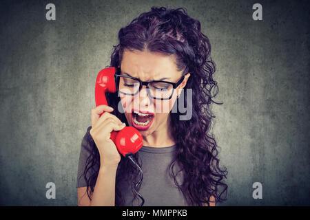 Jeune femme en colère crier au téléphone Banque D'Images