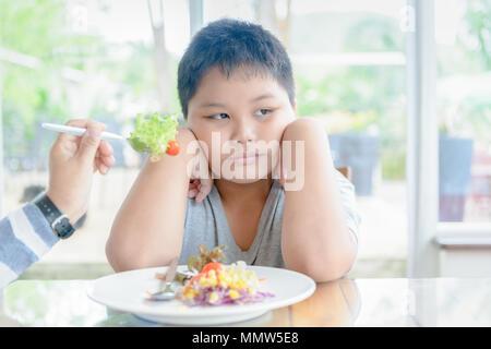 L'anorexie, obésité fat boy avec expression de dégoût contre légumes, refusant food concept Banque D'Images