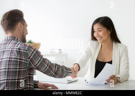 Smiling asian businesswoman handshaking businessman embauche ou tr Banque D'Images