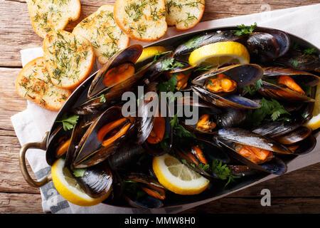 Moules à la française citron, le persil et l'ail close-up dans une marmite en cuivre et de grillé sur la table supérieure horizontale. Vue de dessus Banque D'Images