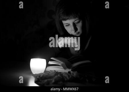 Photo en noir et blanc. Femme lisant un livre à la lumière d'une bougie.