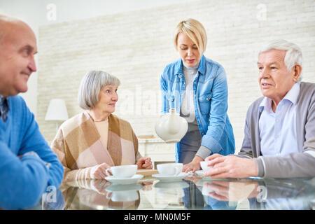 Woman pouring tea pour les patients à domicile aide à la vie assis à table et discuter. Banque D'Images