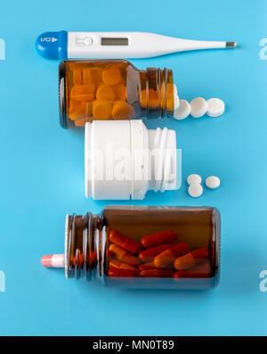 Diverses bouteilles de pilules et de comprimés ronds blancs sur fond bleu Banque D'Images