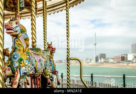 Une vue de la jetée de Brighton avec le traditionnel carrousel cheval sur la jetée et de la British Airways j360 tour d'observation à la distance. Banque D'Images