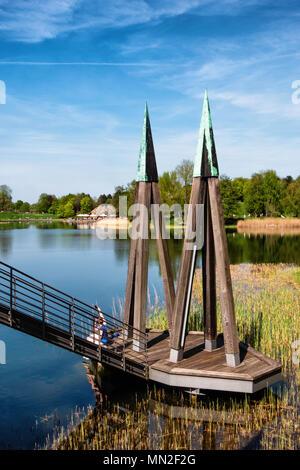 Britzer Garten, Neukölln, Berlin, Allemagne. 2018.jeune couple s'asseoir à côté de soleil rhizomatiques pont avec lake & Cafe am voir en arrière-plan. Banque D'Images