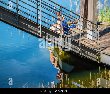Britzer Garten, Neukölln, Berlin, Allemagne. 2018.jeune couple s'asseoir à côté de soleil rhizomatiques pont sur traquil lake Banque D'Images
