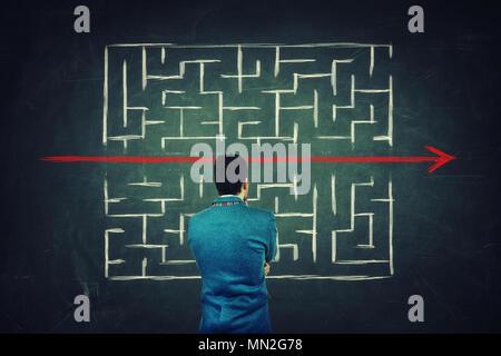 Vue arrière d'un homme perplexe devant un tableau noir, trouver une solution pour échapper à labyrinthe. D'enfreindre les règles, comme une ligne rouge percer la Banque D'Images