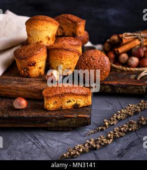 Des muffins avec des fruits secs et raisins secs sur une planche de bois brun, noir tableau