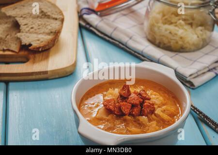 Soupe de choucroute cuisine tchèque avec de la saucisse et les pommes de terre dans un plat blanc sur bleu table bois Banque D'Images