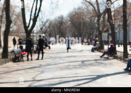 Image floue de personnes marchant sur une journée ensoleillée. Banque D'Images