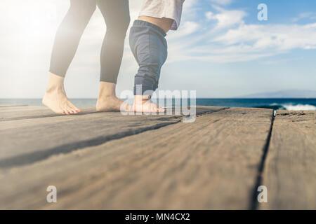 Bébé garçon marchant sur la plage dans la belle journée d'été. Mère avec petit garçon apprendre à marcher sur la plage en bois trottoir.