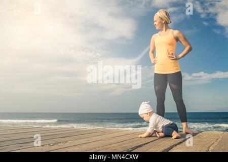 Bébé Garçon jouant avec la mère sur la plage, journée d'été. Supermaman avec petit garçon apprendre à marcher sur la plage en bois trottoir.