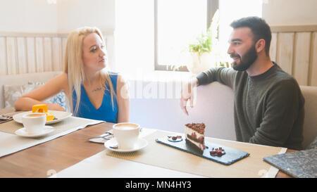 Jeune homme et femme blonde prend la tasse de café au café Banque D'Images