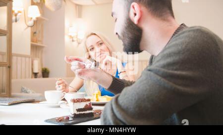 Heureux couple prend des desserts et parler au café Banque D'Images