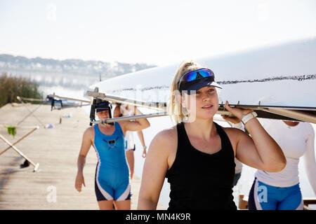 Les rameurs femelle transportant scull sur dock ensoleillée Banque D'Images