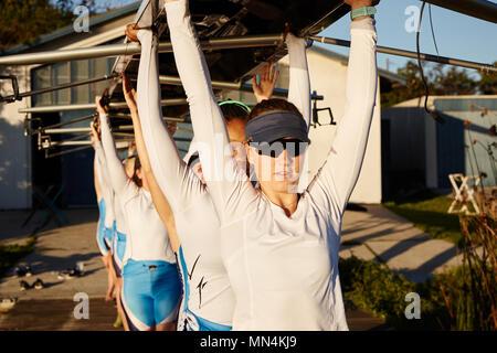 Confiant, déterminé l'équipe d'aviron de godille de levage femelle passage sur dock ensoleillée Banque D'Images