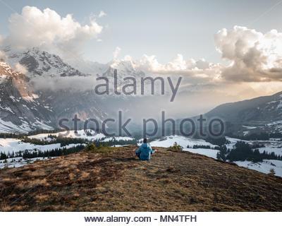 Seul homme assis en face d'une vaste gamme de montagne dans les alpes suisses en méditant, lever de la lumière et de montagnes couvertes de neige Banque D'Images