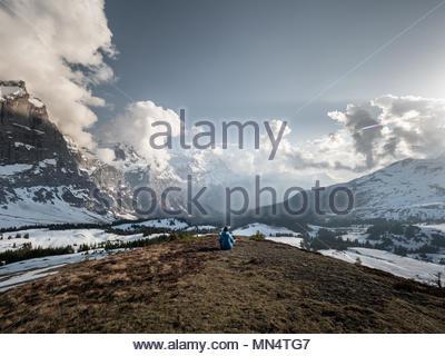 Un homme méditant dans paysage de montagne grand ouvert en face de grandes alpes suisses des pics de montagne et la montagne eiger, pour des concepts comme la relaxation, l sain Banque D'Images