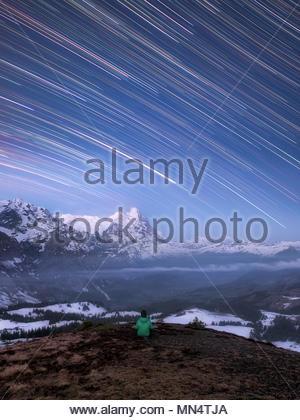 Un homme assis sous le ciel nocturne dans les montagnes de méditer, étoile filante comme star trails à partir de la rotation de la terre et couverts de neige, paysage alpin Banque D'Images