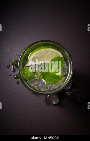 Boisson d'été Tradition mojito avec de la chaux et de menthe en verre sur fond noir en sombre Banque D'Images