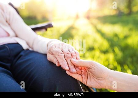 Petite-fille méconnaissable holding hand d'une vieille grand-mère en fauteuil roulant dans la nature au printemps. Banque D'Images