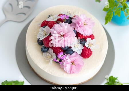 Summer berry cheesecake vegan. Des matières premières, ce gâteau est décoré avec des framboises, bleuets et fleurs fraîches et fait un délicieux dessert. Banque D'Images