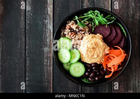 Bol de nourriture végétarienne saine d'hummus, haricots, riz sauvage, betteraves, carottes, concombres et pousses de pois. Voir ci-dessus sur le bois sombre. Banque D'Images