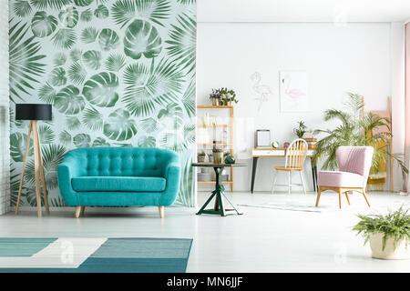 Cette chambre spacieuse dispose d''à côté de la table bleu vert rose contre le papier peint et président de l'espace de près de Banque D'Images