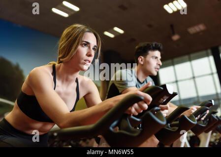 Jolie femme et l'homme autour de la salle de sport, l'exercice de jambes faisant cardio vélo vélos. Dans un couple de spinning portant des vêtements de sport. Banque D'Images