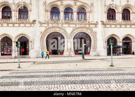 3 mars 2018: Lisbonne, Portugal - la façade à arcades de la gare Rossio, un couple à faire leur chemin à l'entrée. Au premier plan un pélican c Banque D'Images