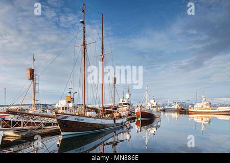 13 avril 2018: Husavik (Islande). Le port de Husavik dans le Nord de l'Islande, avec les navires des baleines reflète dans l'eau calme. Banque D'Images