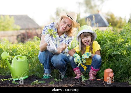 Mère et fille la plantation des plants de fraises dans l'heure d'été