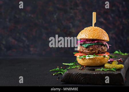 Big sandwich - hamburger burger de boeuf, tomate, basilic fromage et roquette. Banque D'Images