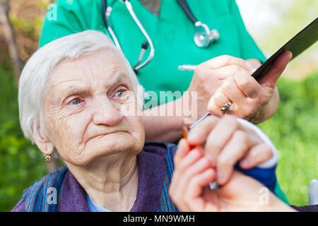 Personnes âgées femme malade recevant les pilules d'une infirmière, médecin écrit prescription médicale dans l'arrière-plan Banque D'Images