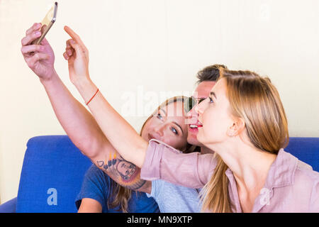 3 mecs assis sur un canapé bleu prendre des photos avec un téléphone. Deux femmes avec de longs cheveux blonds. Le garçon avec des lunettes et des tatouages Banque D'Images