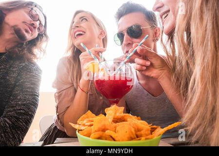 Quatre hommes et femmes s'amuser ensemble potable amitié tous avec le même vase en verre avec des fruits orange rouge. partie du temps avec fond clair pour youn Banque D'Images