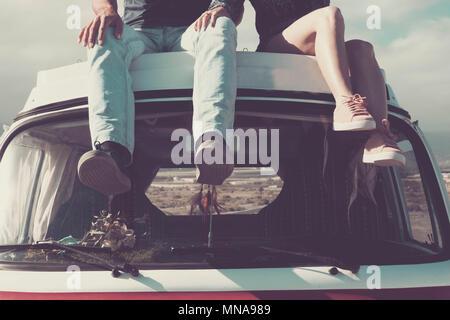 Profitez de l'vanlife. deux paires de jeunes jambes assis sur le haut d'un vintage retro van profiter de la journée. Transport et découvrez de nouveaux endroits comme un désert en b Banque D'Images