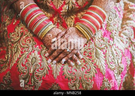 Le gros plan de la mariée indienne avec de beaux saree rose montrant mehndi (henné) part avec beaucoup de paillettes bracelets bangles () sur son poignet Banque D'Images