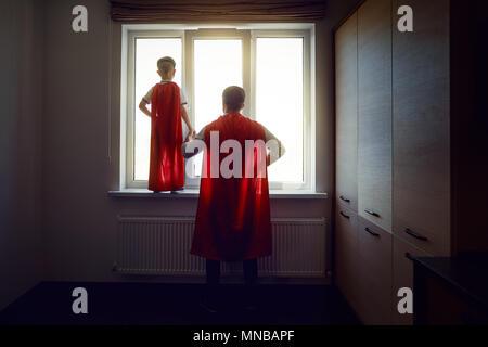 Père et fils à la fenêtre dans la chambre. Banque D'Images