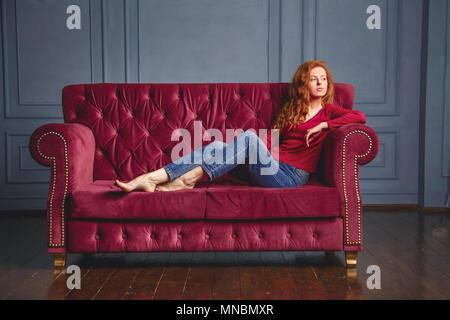 Jeune femme riche couché sur la table rouge