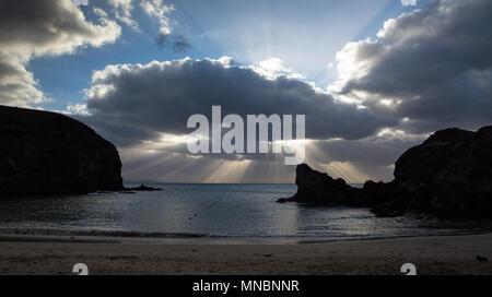 LANZAROTE, îles Canaries, Espagne: rayons de soleil à travers un nuage sur l'horizon à plage de Papagayo. Banque D'Images