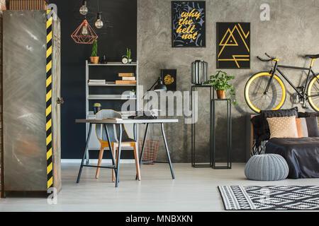 Appartement dans un style industriel avec lit, bureau et armoire métallique Banque D'Images