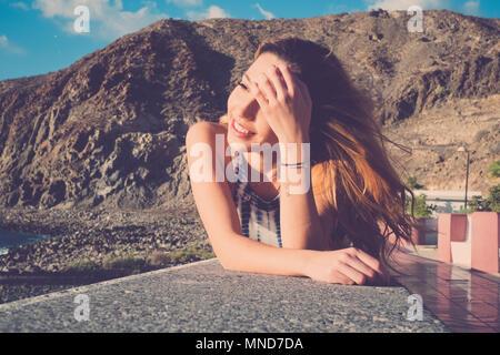 Les cheveux longs l'espagnol jeune femme erlaxing s'étendit sur un mur près de la plage. La lumière du soleil sur sa beauté visage, sourire et profiter du temps. Banque D'Images